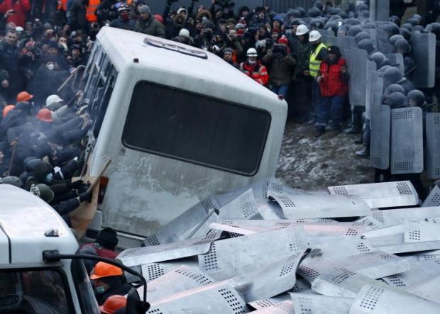 Люди расталкивают милицейские автобусы