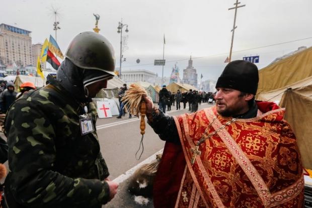 Священник освящает водой участников Евромайдана