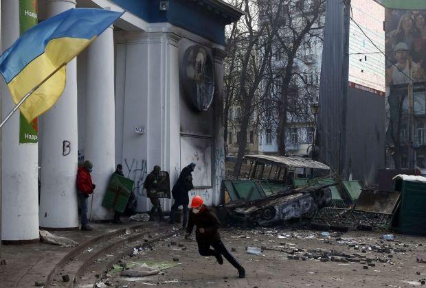 Митингующий бежит в укрытие во время столкновений с милицией / REUTERS